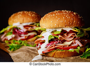 Sesame seeded sandwiches with ham, lettuce, cheese and tomato.