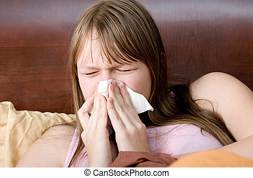 Sick with flu teenager girl in bed sneezing , allergy , illness.