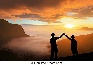 silhouette of Young family happy look sunrise on the top mountain