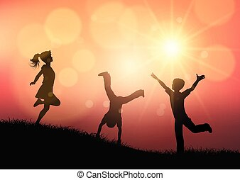 Silhouettes of children playing in sunset landscape
