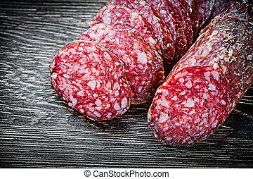Sliced summer sausage on wooden board