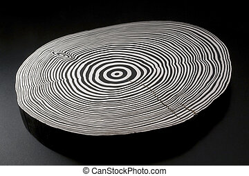 piece of wood with black and white painted annual rings in dark back