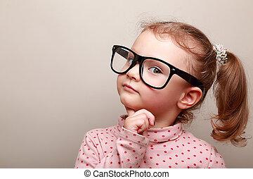 Smart dreaming kid girl in glasses looking. Closeup portrait