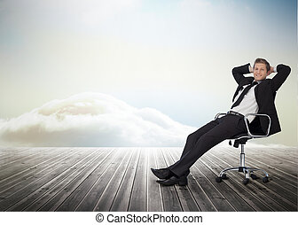 Smiling businessman sitting in a swivel chair on wooden boards with heavenly backdrop