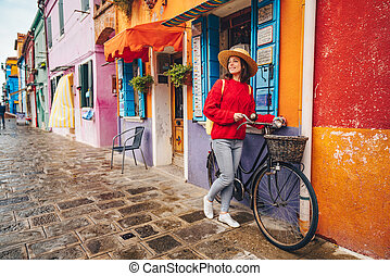 Smiling girl with a bike in Italy