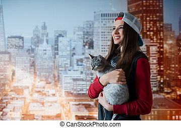 Smiling girl with a cat in hands