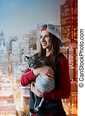 Smiling girl with a cat in hands. Vertical photo.
