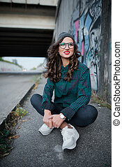 Smiling girl with red lips sitting on the highway under a bridge on a background of graffiti. Curly hair and glasses for vision. Dressed in a green shirt, blue jeans and white sneakers.