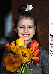 Smiling kid girl with colorful tulips in hands