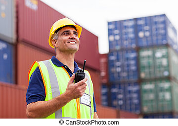 middle aged warehouse worker holding radio
