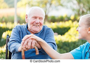 Young happy doctor giving support to his elderly patient.