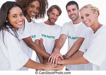 Smiling volunteer group putting hands together on white background