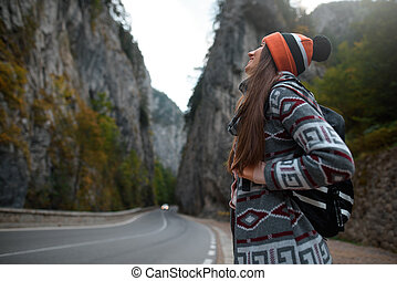Smiling young girl with a backpack near a road in the mountains. Looks up at landscape.