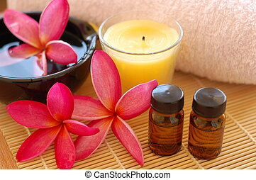 Plumerias, aroma therapy oil, therapy candle and towel placed on bamboo mate at spa.