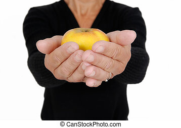 Two hands with an yellow apple