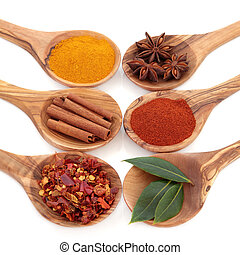 Bay leaf herb, turmeric, chili flakes, star anise, cinnamon sticks and cayenne pepper spice in olive wood spoons over white background.