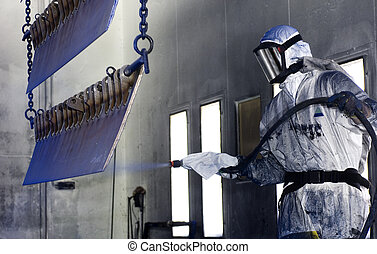 Man in a protective suit, wearing a gas mask spray painting steel semi finished parts in a production environment