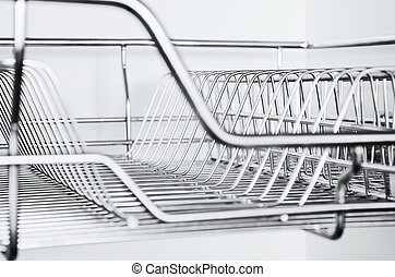 Close-up of stainless steel dish rack inside kitchen cabinet