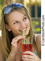 A young lady drinking a tall drink outside enjoying the summer sunshine.
