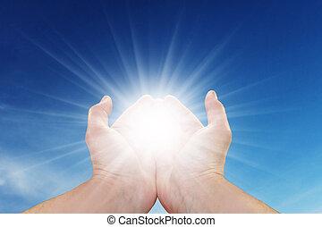 Mans hands holding sun rays