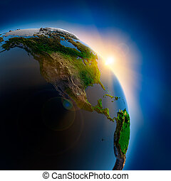 The sun's rays from the rising sun illuminate the earth in outer space