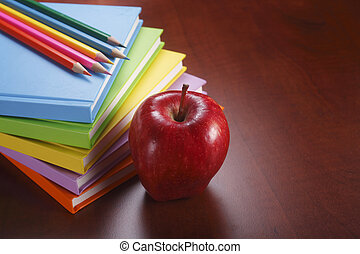 A stack of books with some pencils and an apple.