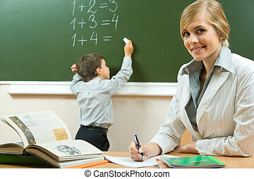 Portrait of pretty teacher sitting at the table on the background of schoolboy