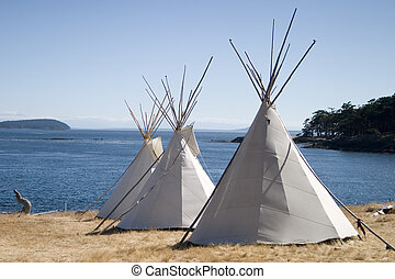 Three teepees (aka tipis) are lined up in a row in front of water. These teepees are used at a summer camp. Teepees were one form of traditional shelter used by native americans.