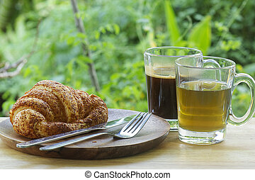 Thai Black Coffee and hot Tea with croissant bread on  Wooden Bar