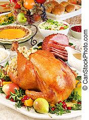 Thanksgiving dinner with roast turkey, baked ham, pumpkin pie, gravy, dinner rolls, cranberry chutney etc.