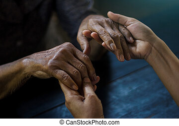 The daughter  holding hand and takes care mother elderly that is alzheimer and parkinson's patient on dark background.