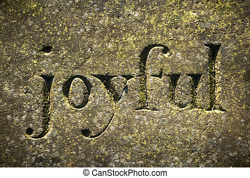 """The word """"Joyful"""" etched in a old weathered stone."""