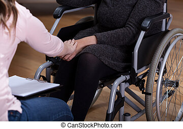 Horizontal view of therapist comforting disabled woman