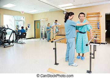 Physical therapists assisting patients in hospital gym