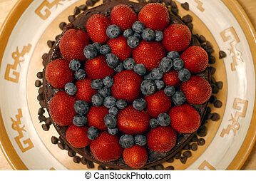 The strawberries and blueberries are laid over a raspberry spread on a chocolate torte. Delicious and fulfilling!