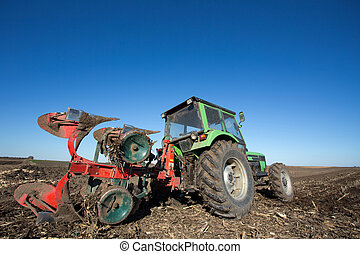 Tractor with plowing equipment in the field