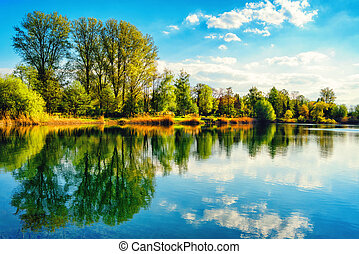 Tranquil lakeshore landscape with blue sky and water