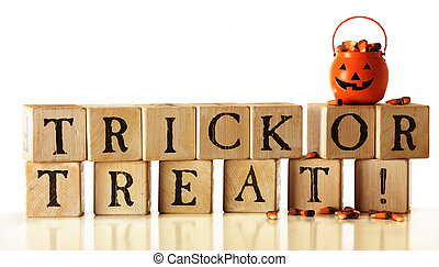 """Rustic alphabet blocks arranged to say, """"Trick or Treat!"""" A pumpkin-bucket overflowing with candy corn sits on top. Isolated on white."""