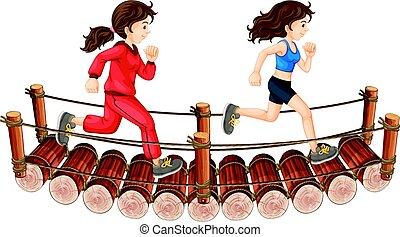 Two girls running on the wooden bridge