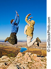Two hikers jumping cheerfully on mountain summit in clear sunny weather