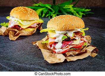 Two sandwiches with ham, cheese, tomatoes, lettuce on dark background.