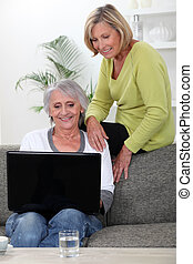 two senior friends relaxing at home