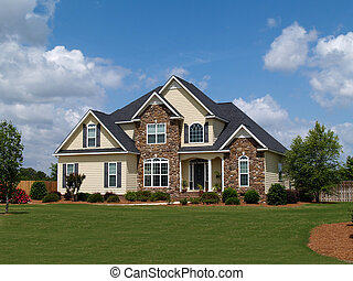 Two story residential home with both stone and board siding on the facade.
