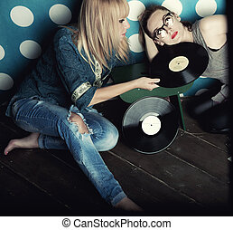 Two young women with vinyl records in his hands