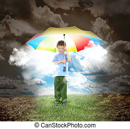A young child is holding a rainbow umbrella with sunshine glowing out. The boy is surrounded with a dried up landcsape and grass under his shoes for a home concept.