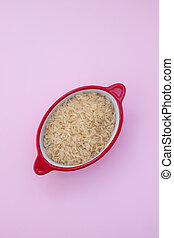 uncooked rice in red bowl on pink background