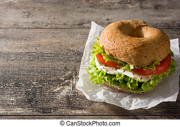 Vegetable bagel sandwich with tomato, lettuce, and mozzarella cheese on wooden table. Copy space