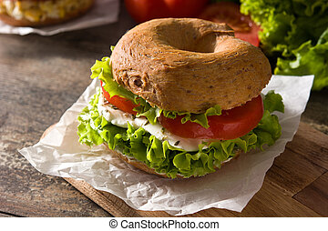 Vegetable bagel sandwich with tomato, lettuce, and mozzarella cheese on wooden table.