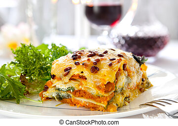 Vegetarian lasagne topped with toasted pine nuts and melting cheeses. With salad and red wine.