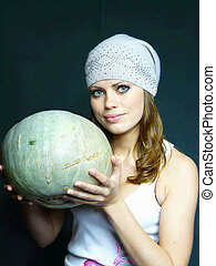 very beautiful young blue-eyed girl with a pumpkin in hands